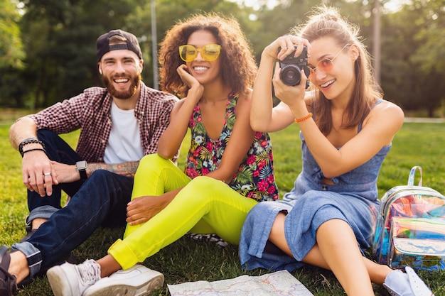 Glückliche junge gesellschaft von freunden, die park, mann und frauen sitzen, die spaß zusammen haben, mit kamera reisen, sprechen, lächeln