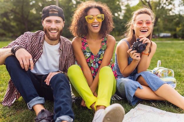 Glückliche junge gesellschaft von freunden, die park sitzen, mann und frauen, die spaß zusammen haben, mit kamera reisen,
