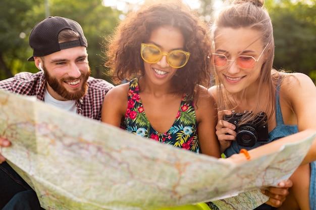 Glückliche junge gesellschaft von freunden, die parkreisen sitzen und in kartenbesichtigung schauen, mann und frauen, die spaß zusammen haben