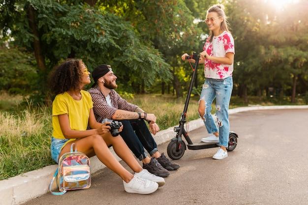 Glückliche junge gesellschaft von lächelnden freunden, die im park auf gras mit elektrischem tretroller sitzen, mann und frauen, die spaß zusammen haben