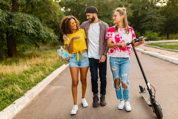 Glückliche junge gesellschaft von lächelnden freunden, die im park mit elektrischem tretroller, mann und frauen gehen, die spaß zusammen haben
