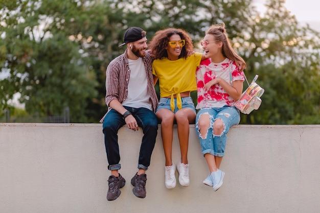 Glückliche junge gesellschaft von lächelnden freunden, die im park sitzen, mann und frauen, die spaß zusammen haben