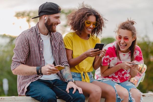 Glückliche junge gesellschaft von lächelnden freunden, die park mit smartphones, mann und frauen sitzen, die spaß haben sitzen