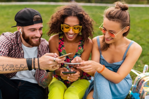 Glückliche junge gesellschaft von lächelnden freunden, die park mit smartphones, mann und frauen sitzen, die spaß zusammen haben