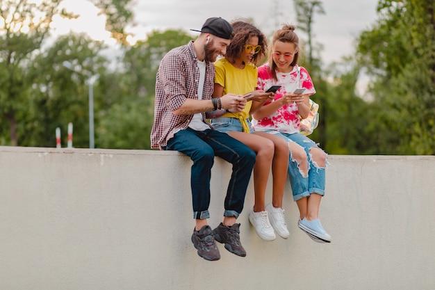 Glückliche junge gesellschaft von lächelnden freunden, die park mit smartphones sitzen