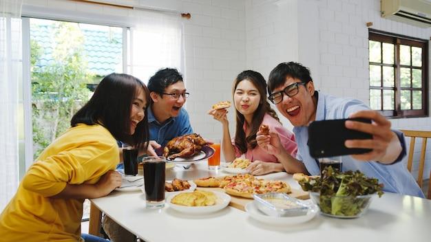 Glückliche junge gruppe, die zu hause zu mittag isst. asia familienfeier, die pizza essen isst und selfie mit ihren freunden auf geburtstagsfeier am esstisch zusammen im haus macht. festurlaub und zusammengehörigkeit