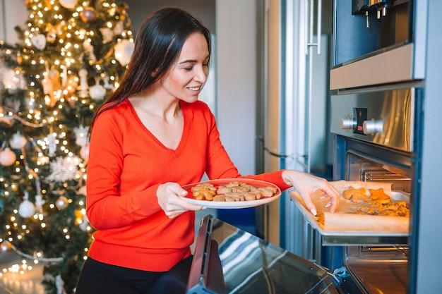Glückliche junge hausfrau, die ingwerplätzchen in weihnachten zu hause vorbereitet