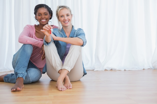 Glückliche junge housemates, die ihre schlüssel des neuen hauses zeigen