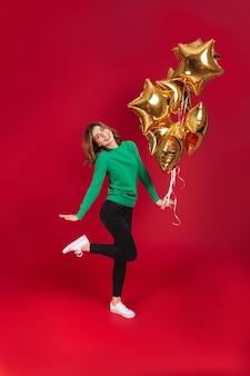 Glückliche junge hübsche frau, die ballone hält.