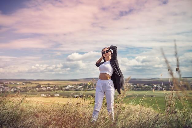 Glückliche junge hübsche frau, die im sommer die landschaft in der nähe der grünen wiese genießt?