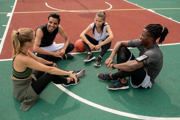 Glückliche junge interkulturelle freunde, die das letzte basketballspiel besprechen, während sie nach dem training auf dem platz sitzen