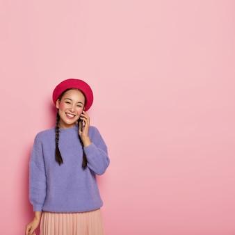 Glückliche junge japanerin entspannt sich während des telefongesprächs, bespricht etwas angenehmes, trägt helle kleidung