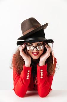 Glückliche junge kaukasische dame, die hüte durch verkauf trägt