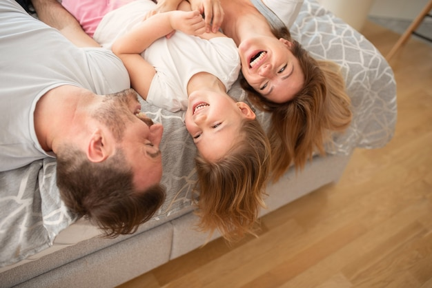 Glückliche junge kaukasische eltern lachen, während sie mit ihrer kleinen tochter auf ihrem bett liegen