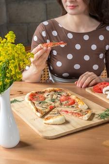Glückliche junge kaukasische frau, die eine pizza mit pilzen in einem café oder zu hause isst.