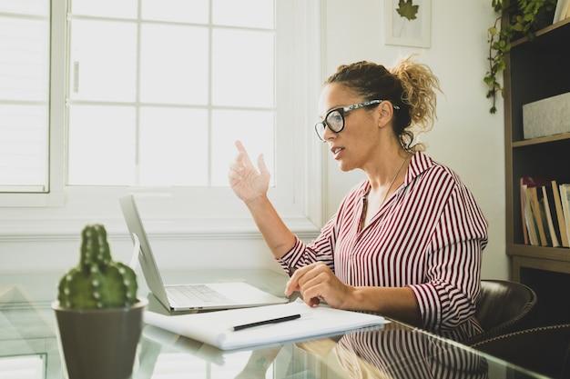 Glückliche junge kaukasische geschäftsfrau, die lächelnd online arbeitet und webinar-podcasts auf dem laptop sieht und bildungskurskonferenzen anruft, machen notizen am schreibtisch sitzen, e-learning-konzept