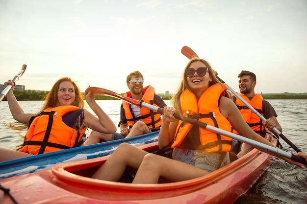 Glückliche junge kaukasische gruppe von freunden, die auf dem fluss mit sonnenuntergang im hintergrund kajak fahren. spaß an der freizeitbeschäftigung. glückliches männliches und weibliches modell, das auf dem kajak lacht. sport, beziehungskonzept.