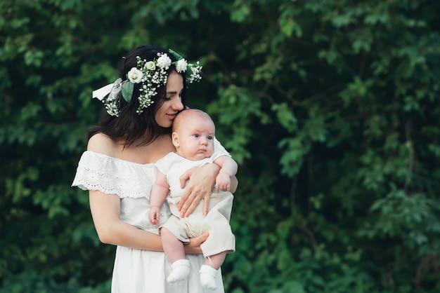 Glückliche junge kaukasische mutter umarmt ihren neugeborenen sohnjungen