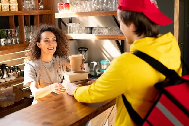 Glückliche junge kellnerin des restaurants oder des cafés, das ein glas kaffee auf kartonbehälter setzt