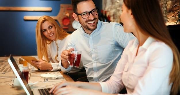 Glückliche junge kollegen von der arbeit, die im restaurant verkehren