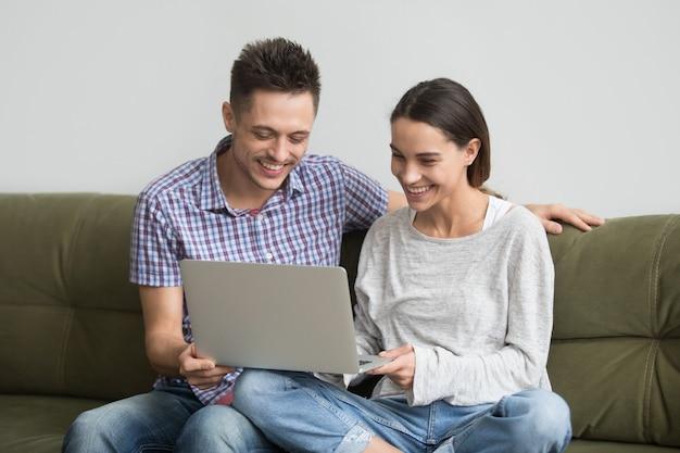 Glückliche junge lachende paare, während videoanruf auf laptop gemacht wird