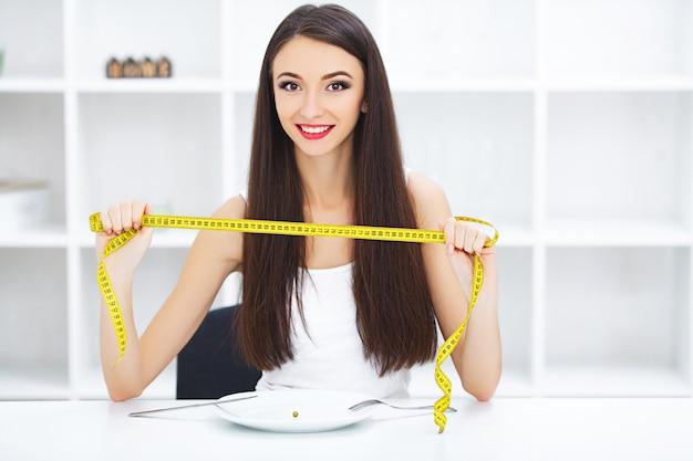 Glückliche junge lächelnde frau ungefähr, zum einer erbsenhalteplatte und -gabel mit maßband zu essen.