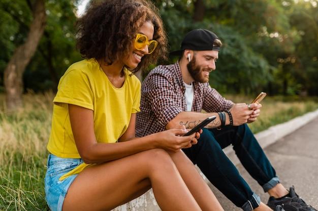 Glückliche junge lächelnde freunde sitzen park mit smartphones, mann und frau, die spaß zusammen haben