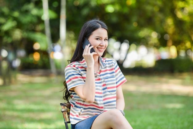 Glückliche junge lächelnde unterhaltungshandykommunikation des frauentelefons auf parkfrau, die mit zelltelefon benennt