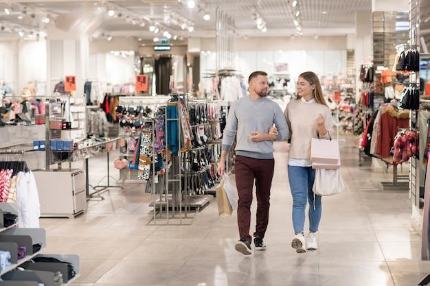 Glückliche junge lässige datteln, die papiertüten tragen, während sie entlang der kleidungsabteilung während des einkaufs in der mall gehen