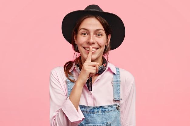 Glückliche junge landfrau in lässigem outfit und hut, macht shush-geste, hat positiven gesichtsausdruck, erzählt geheimnis zum begleiter