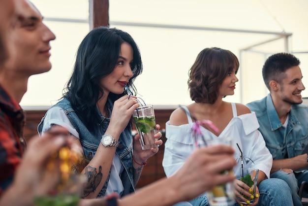 Glückliche junge leute, die cocktails trinken und sich mit freunden auf dem dach entspannen