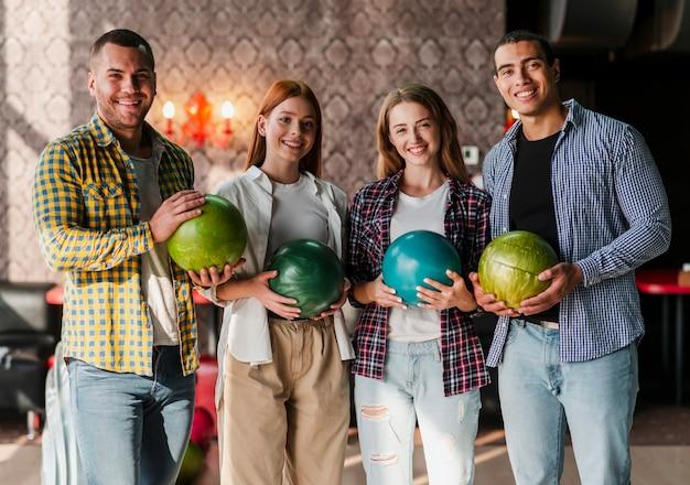 Glückliche junge leute, die in einem bowlingspielverein stehen