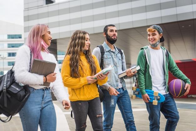 Glückliche junge leute, die sich im freien treffen und gesichtsmasken während der covid-19-pandemie tragen