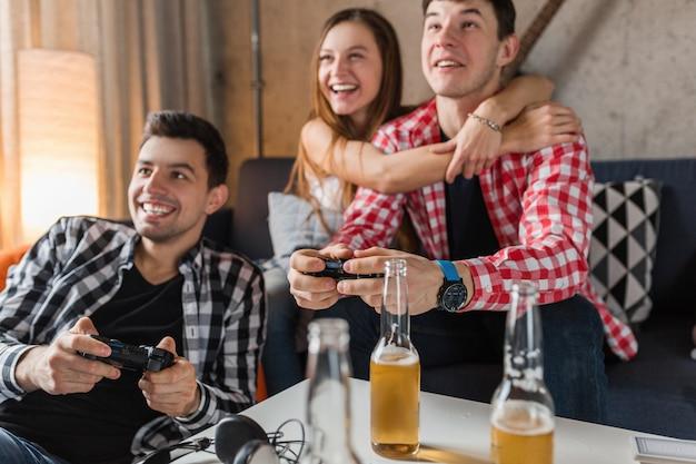 Glückliche junge leute, die videospiele spielen, spaß haben, freunde feiern zu hause, schließen hände, die joystick, hipster-gesellschaft zusammenhalten, lächelnd, positiv, lachend, wettbewerb, bierflaschen auf tisch