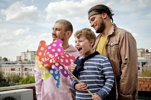 Glückliche junge leute und kleiner junge stehen auf dem dach des gebäudes mit regenbogen-windrad in den händen