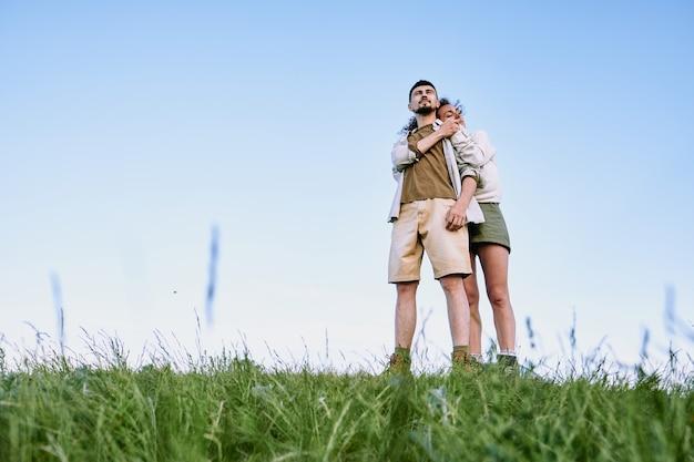 Glückliche junge liebevolle frau, die zu ihrem ehemann steht und ihn während ihrer ruhe auf dem land gegen blauen himmel umarmt