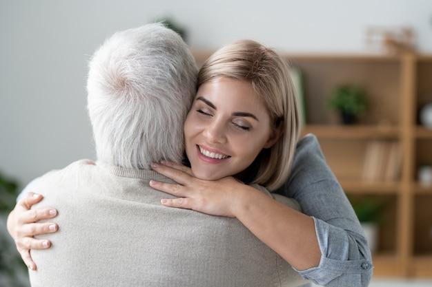 Glückliche junge liebevolle frau mit zahnigem lächeln, die ihren älteren vater umarmt, während sie liebe und fürsorge ausdrückt