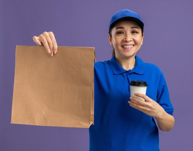 Glückliche junge lieferfrau in blauer uniform und mütze, die papierpaket und pappbecher mit einem lächeln auf dem gesicht hält, das über lila wand steht