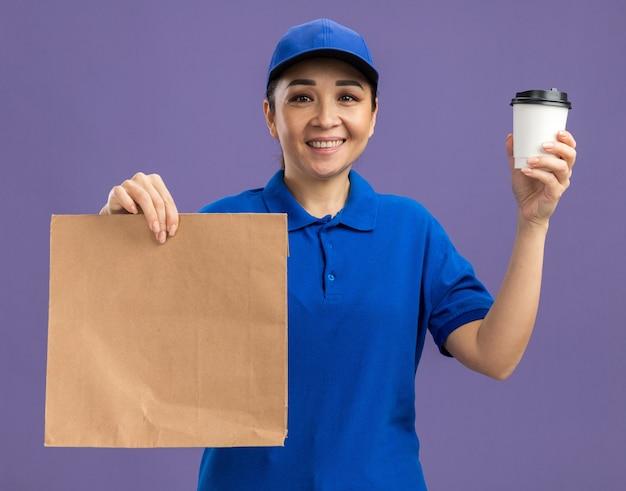 Glückliche junge lieferfrau in blauer uniform und mütze, die papierpaket und pappbecher mit einem lächeln im gesicht hält