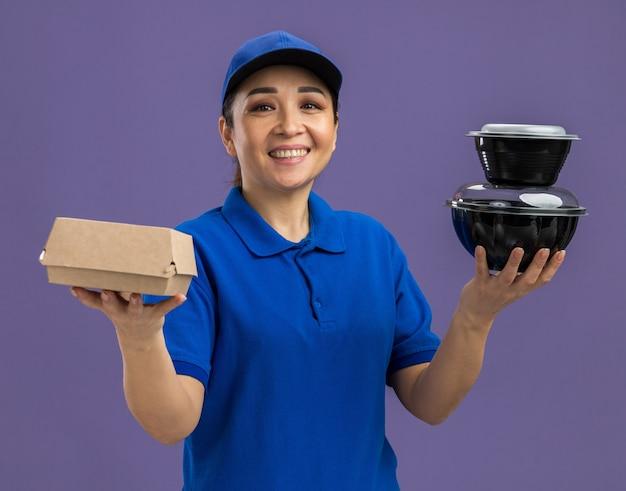 Glückliche junge lieferfrau in blauer uniform und mütze mit lebensmittelpaketen, die fröhlich lächeln