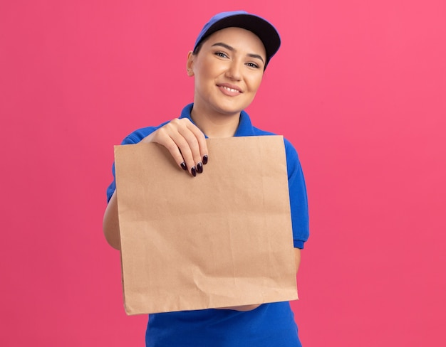 Glückliche junge lieferfrau in der blauen uniform und in der kappe, die papierpaket hält, das vorne lächelt, das fröhlich über rosa wand steht