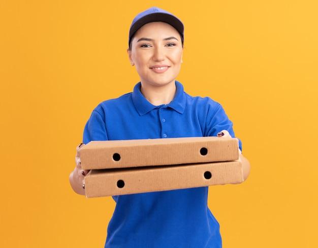 Glückliche junge lieferfrau in der blauen uniform und in der kappe, die pizzaschachteln hält, die vorne lächelnd zuversichtlich über orange wand stehen
