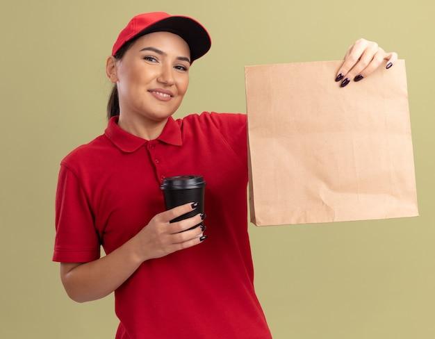 Glückliche junge lieferfrau in der roten uniform und in der kappe, die papierpaket und kaffeetasse hält, die vorne mit lächeln auf gesicht steht, das über grüner wand steht