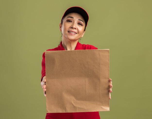Glückliche junge lieferfrau in roter uniform und mütze, die papierpaket mit einem lächeln im gesicht hält