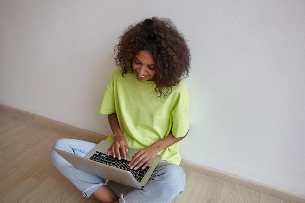 Glückliche junge lockige frau mit dunkler haut, die mit freunden auf laptop plaudert, mit gekreuzten beinen sitzt, jeans und gelbes t-shirt trägt
