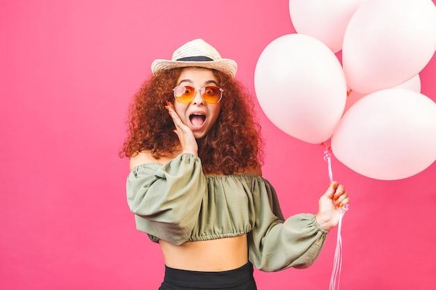 Glückliche junge lockige lächelnde frau mit luftballons lokalisiert über rosa hintergrund