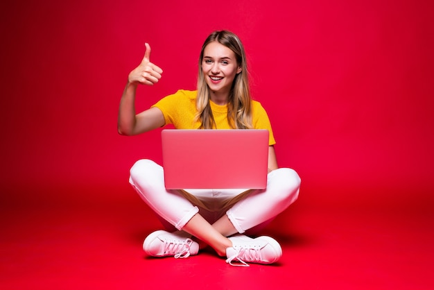 Glückliche junge lockige schöne frau, die auf dem boden mit gekreuzten beinen sitzt und laptop auf roter wand verwendet.