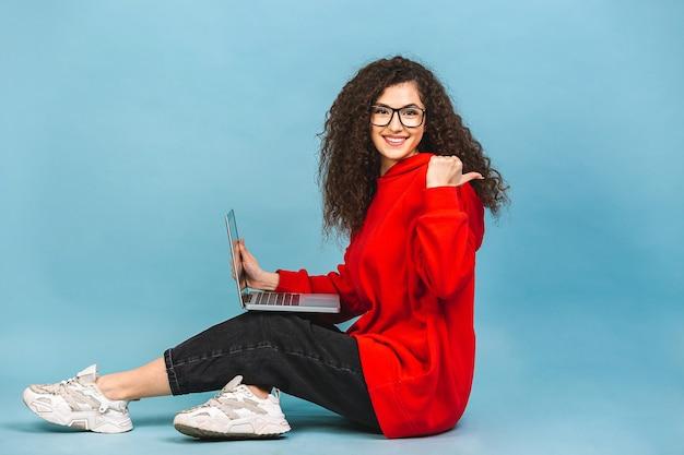 Glückliche junge lockige schöne frau, die auf dem boden mit gekreuzten beinen sitzt und laptop lokalisiert auf blauem hintergrund verwendet.