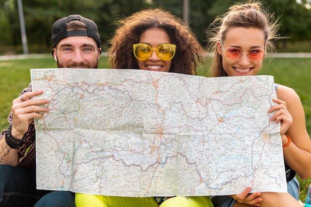 Glückliche junge lustige gesellschaft von freunden touristen, die sich hinter karte in sonnenbrillen, mann und frauen verstecken, die spaß zusammen haben, reisen