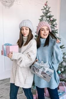 Glückliche junge mädchen, die pullover mit geschenken nahe dem weihnachtsbaum tragen